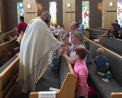 Local Catholics rejoice at once again gathering for Mass, receiving the Eucharist